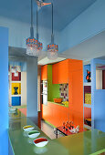 Orange cupboards and green breakfast bar in kitchen with blue walls