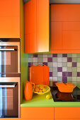 Orange kitchen cupboards with green worksurface and fitted appliances