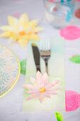 Mit Papierblume beklebte Bestecktasche auf dem Tisch