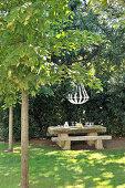 Stone bench and table below chandelier in garden