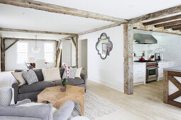 Rustic wooden beams in open-plan interior with view into kitchen