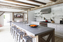 Metal stools at island counter in open-plan country-house kitchen