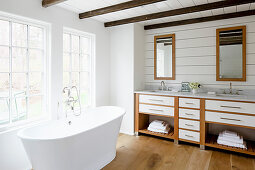 Free-standing bathtub below lattice windows in rustic bathroom