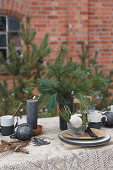 Table set for Christmas with fir branches and black candles