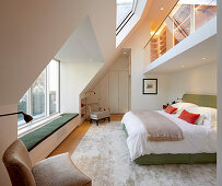 Gallery with glass balustrade in elegant, double-height bedroom