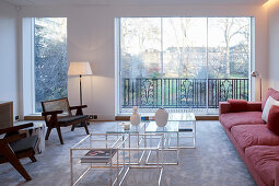 Seating and set of coffee tables in living room with panoramic view of garden