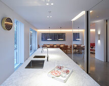 Island counter with marble top and mirrored wall in elegant kitchen with dining area in background