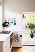 Wandhalterung mit Pfannen neben offener Terrassentür in weißer Küche