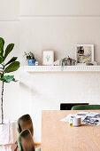 Esstisch mit Stühlen vor Kamin und Zimmerpflanze