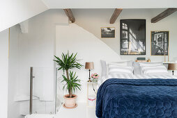 Double bed below rustic wooden beams in white bedroom