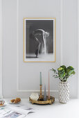 Arrangement of candles and vase on dining table below large photo on pale grey wall