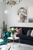 Dark blue sofa with scatter cushions, coffee table and large photos on wall in bright living room