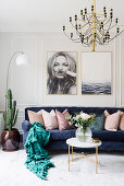 Dark blue sofa with scatter cushions below large photos on wall in bright living room