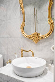 Gilt-framed mirror above countertop sink on marble washstand in bathroom