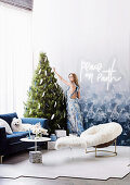 Blond woman decorates Christmas tree in corner of room with cozy seating