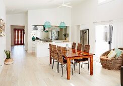 Long dining table with wicker chairs, open kitchen with island in the background