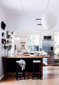 Breakfast counter with bar stools and fridge combination in open kitchen