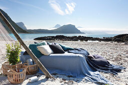 Bed linen and pillows in shades of blue on bed next to baskets on beach