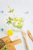 Water with cucumber, edible violas and drinking straws with paper decorations