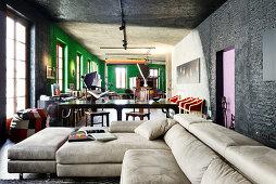 Helle Ledercouch in renoviertem Loft mit schwarzen und grünen Wänden