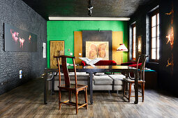 Old wooden table and chairs in renovated loft apartment with black and green walls