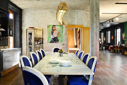 Antique chairs with velvet upholstery around long dining table in renovated loft apartment