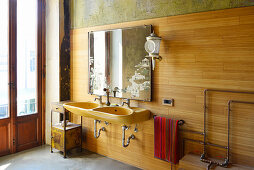 Twin sinks, mirror and wall lamp on wood-panelled bathroom wall