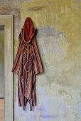 Gestreifter Bademantel an Vintage Wand hängend