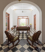 Two rocking chairs in arched doorway leading into living room with chequered floor