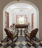 Zwei Schaukelstühle im Bogen zum Wohnzimmer mit Schachbrettboden