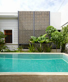Pool in exotic courtyard with wall of ornamental perforated bricks