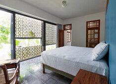 Exotisches Schlafzimmer mit Fensterfront und halboffener Fassade