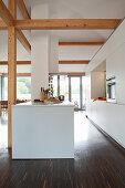 White designer kitchen with island counter in open-plan interior