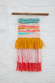 Colourful macrame hanging on white brick wall