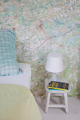 Stool used as bedside table in bedroom with map-patterned wallpaper