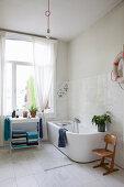 Moderne Badewanne und Regal vor Fenster in hellem Badezimmer