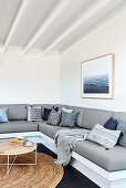 Scatter cushions on grey corner sofa in living room with white walls