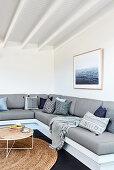 Graues Ecksofa mit Kissen im Wohnzimmer mit weißen Wänden