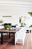 Esstisch mit rustikaler Holzplatte und weißen Rattanstühlen auf überdachter Terrasse