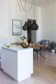 White island counter and rustic dining table in open-plan kitchen