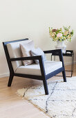 Black armchair with pale upholstery and side table