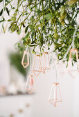 Fairy lights with golden metal ornaments hung from bunch of mistletoe
