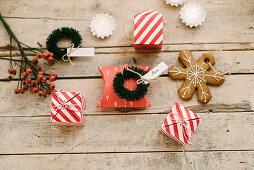 Guest favours in read-and-white striped boxes, gingerbread Christmas-tree decoration and small wreath