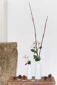 Roses and twigs in two white vases on stool