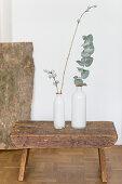 Zwei weiße Vasen mit Eukalyptuszweig auf einem Schemel