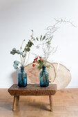 Zwei blaue Vasen mit Zweigen auf einem alten Holzschemel
