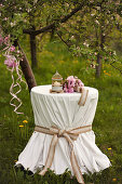 Ornate tablecloth, candle and peonies on round table below tree