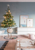 Christmas tree next to sideboard in living room with blue wall