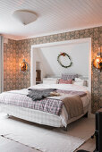 Double bed with head in niche in bedroom with patterned wallpaper