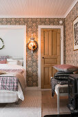 Double bed with head in niche in bedroom with patterned wallpaper and wooden door